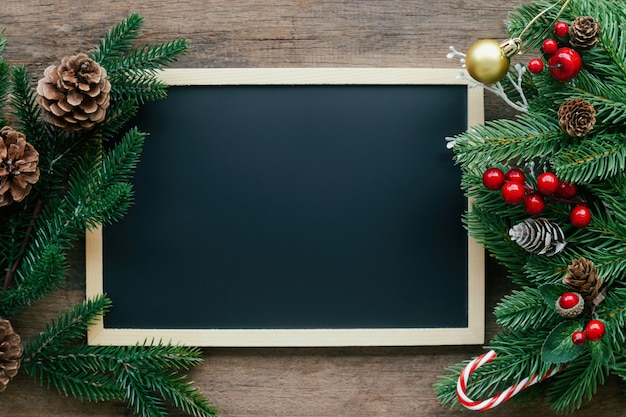 Новогоднее украшение фон с доской или доске, сосновые листья и шишки и холли шары на деревянный стол