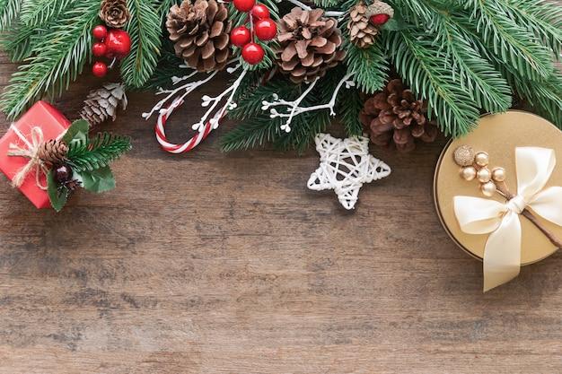 Текстуру старой древесины украшают сосновые листья, сосновые шишки, шарики падуба и подарочная коробка в рождественской теме