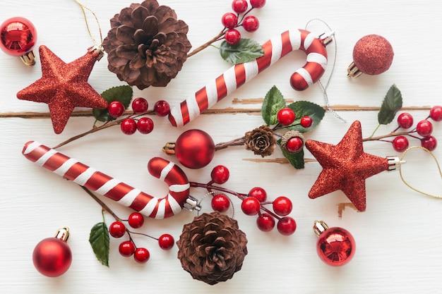 松ぼっくりや針葉樹の円錐形、赤いヒイラギのボール、キラキラ星、キャンディケイン、クリスマスコンセプトで安物の宝石と白い木。クリスマスの壁紙のトップビューフラットレイアウトコピースペースで甘い板背景。