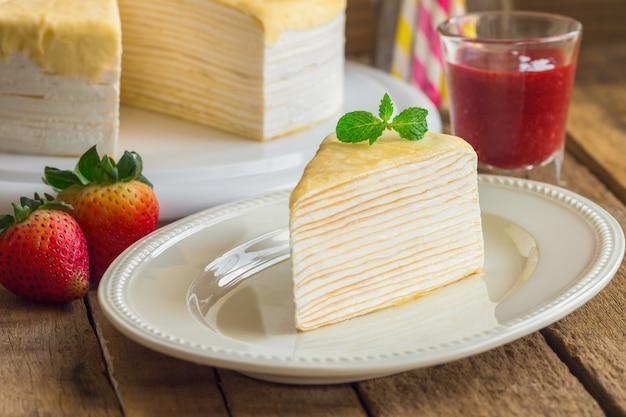 ミントを添えた白いプレートの自家製クレープケーキにイチゴソースを添えて
