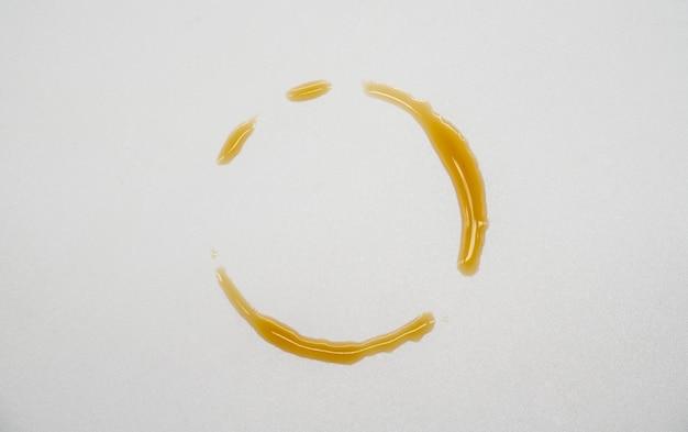 白で隔離される紙の上のステンドグラスのコーヒーボトルのリング