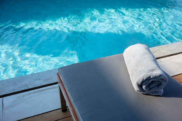 スイミングプールのそばのリラックスできるプールベッドの上にタオルを敷きます。