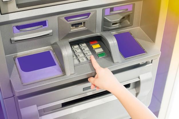 Рука ребенка с помощью банкомата