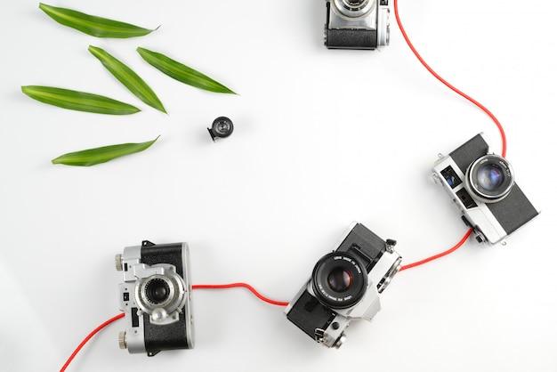 写真機器ヴィンテージ、白い背景の上の緑の葉と作業スペースの概念。