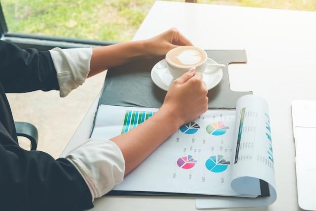 Женщина с цифровым маркетингом принимает горячий кофе при работе с маркетинговой диаграммой