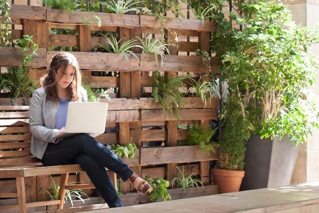 Молодой предприниматель, работающих с ноутбуком на скамейке с растениями фон