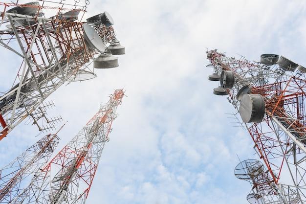 Телекоммуникационная башня с антеннами с голубым небом в утреннем солнечном свете.