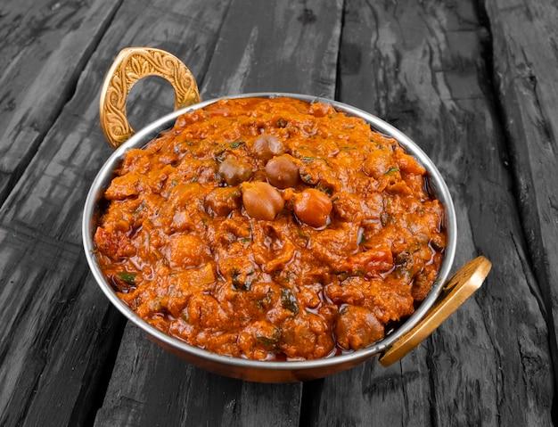 木製の背景にインドの健康料理チャナマサラ