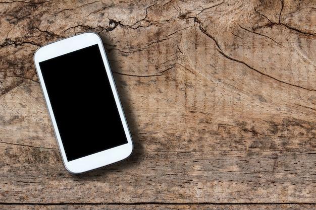 古い木製のテーブル背景にスマートフォン