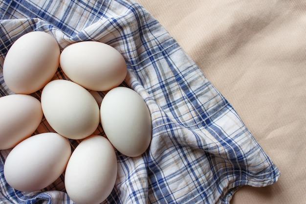 格子縞の生地に新鮮な多くのアヒルの卵