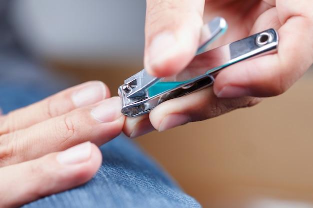 Мужчина подстригает ногти