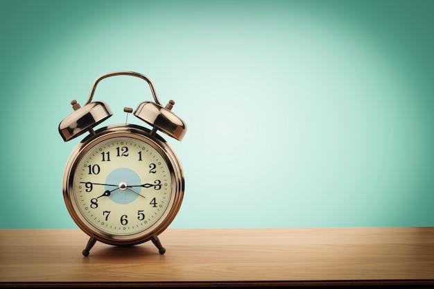 ミントグリーンの壁の背景を持つ古い木製のテーブルの上のレトロな目覚まし時計