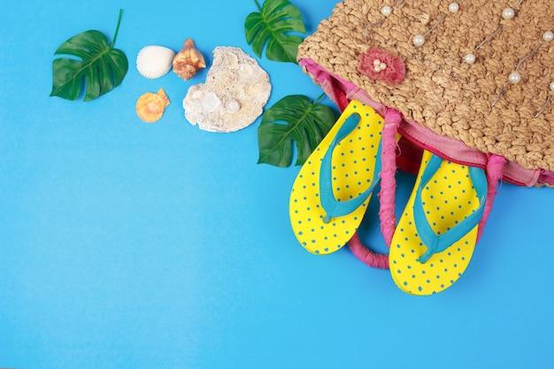 青い色の背景、夏の休日の付属品に編まれたハンドバッグの黄色いサンダル