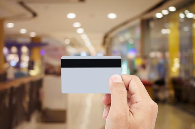 Человек рука кредитной карты на размытия торгового центра
