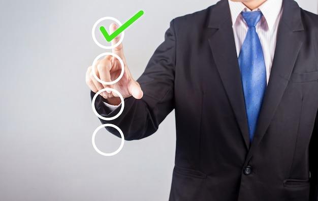 Рука бизнесмена проверяя коробки контрольного списка на серой предпосылке