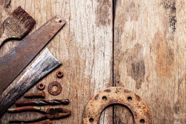 古い木材の背景に古いさびた道具。