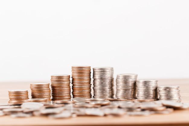 お金の概念を保存するための木製の机の上のコインのスタック