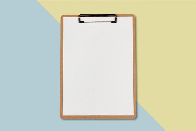 パステルカラーの背景、最小限の概念上の白いシートとクリップボード