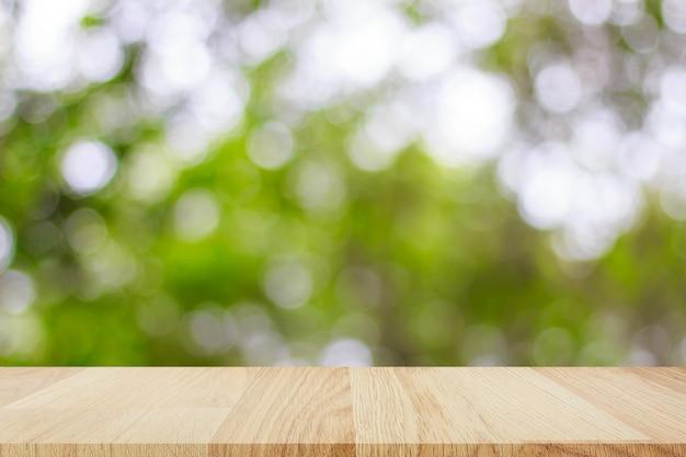あなたの製品のモンタージュの抽象的なボケ味の明るい背景を持つ空の木製テーブル