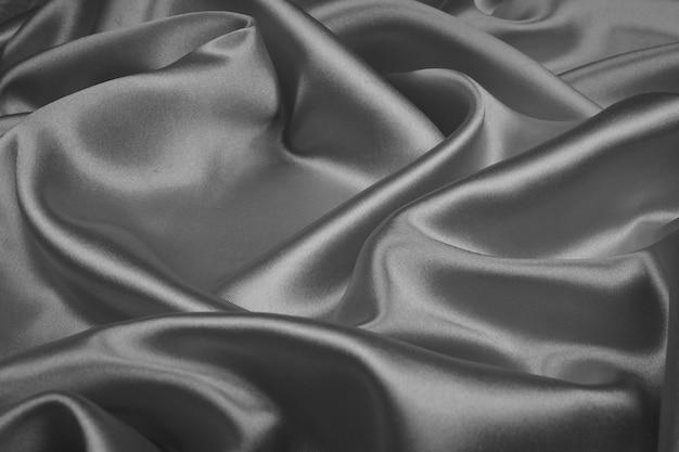 抽象的な背景のグレーのシルクの質感の豪華なサテン