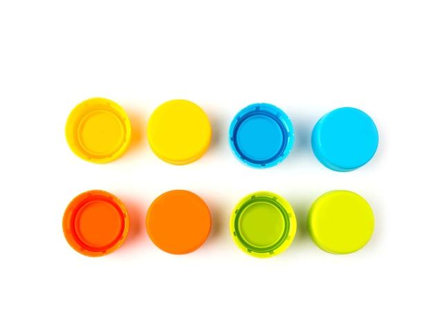 白い背景にカラフルなプラスチックボトルキャップ。選択的なフォーカス