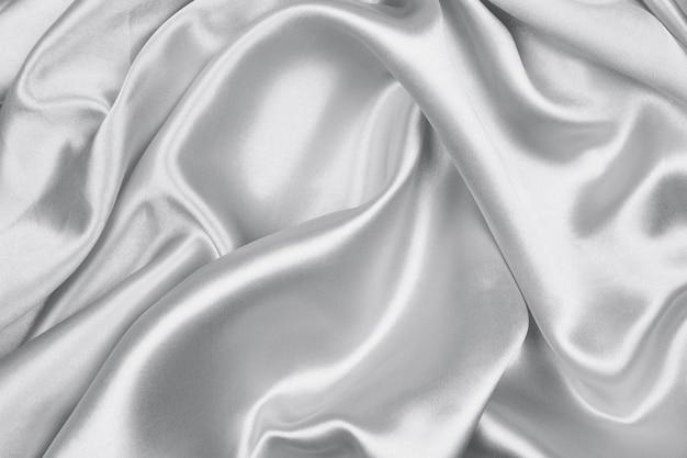 滑らかなエレガントなグレーのシルクやサテンの質感は抽象的な背景として使用することができます
