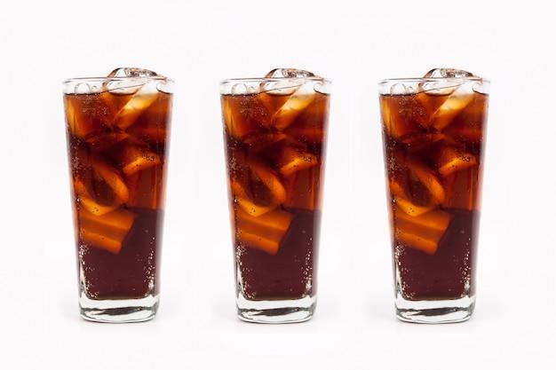 白い背景の上のガラスに氷とコーラを飲む