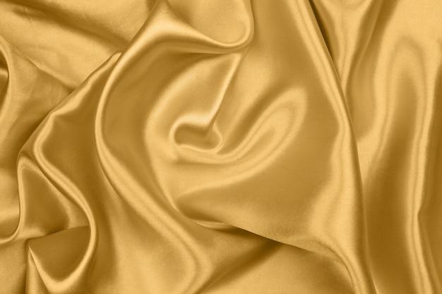 滑らかなエレガントなゴールドのシルクやサテンの質感は抽象的な背景として使用することができます