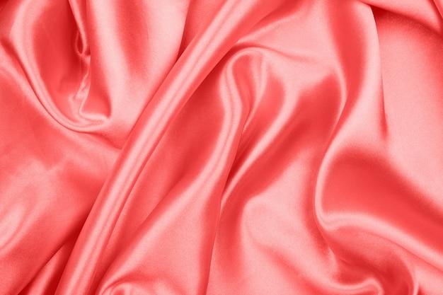 抽象的な背景の赤い絹の質感の豪華なサテン