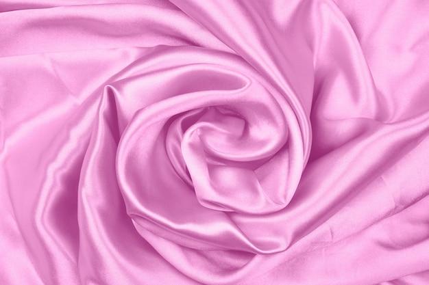 Гладкую элегантную розовую шелковую или атласную текстуру можно использовать в качестве абстрактного фона ткани