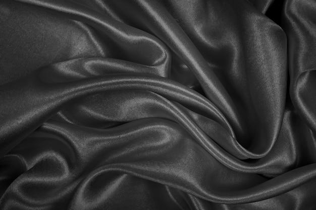 抽象的な背景の黒い絹の質感の豪華なサテン。生地のダークトーン
