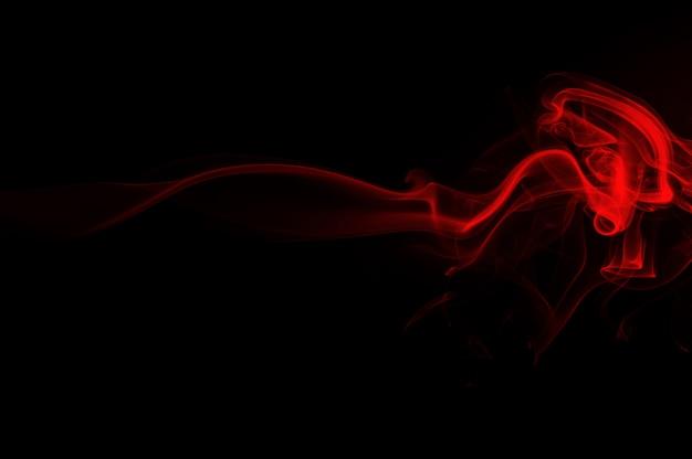 赤い煙は黒い背景に抽象的です。火のデザイン