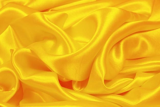 オレンジ色のシルクの質感の抽象的な背景の豪華なサテン