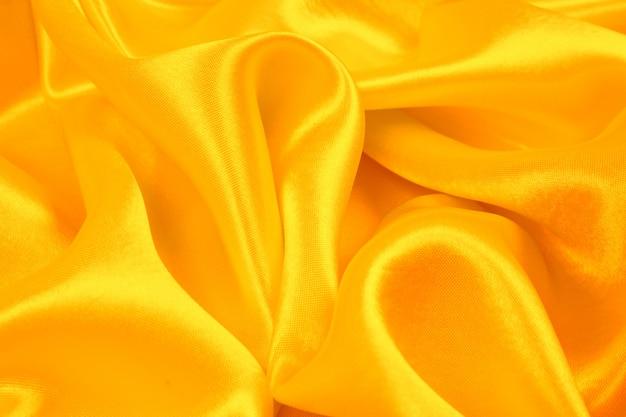 オレンジ色のシルクの質感の抽象的な背景、生地の質感の豪華なサテン