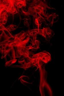 黒い背景に赤い煙の動き。火のデザイン