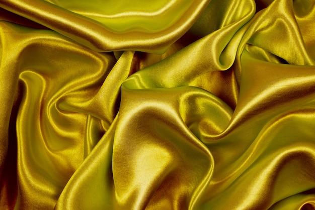 抽象的な背景のゴールデンシルクの質感の豪華なサテン