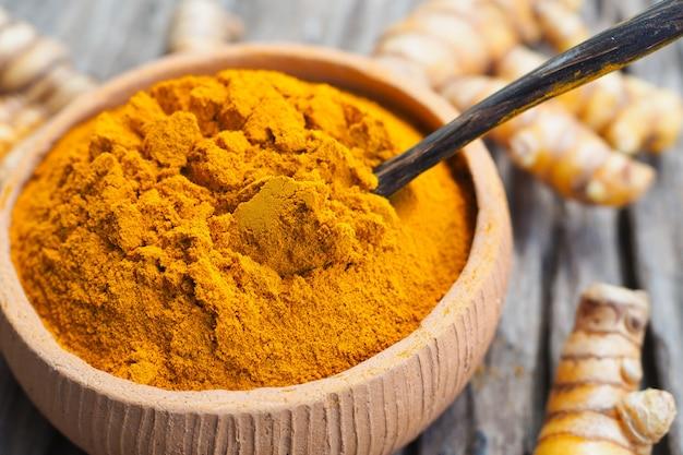 ボウルと古い木製の背景に新鮮なウコンのウコン粉末。ハーブは東南アジア原産です。