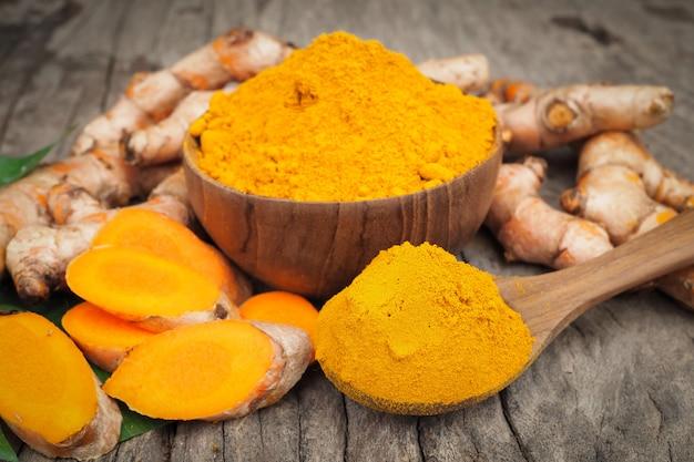 古い木製のテーブルに緑の葉と木のスプーンでウコン粉末と新鮮なウコン。ハーブは東南アジア原産です。