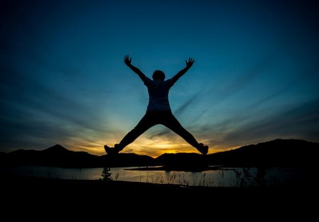 幸せな男のシルエット。自然光、黄金色の夜の光、最後の光。