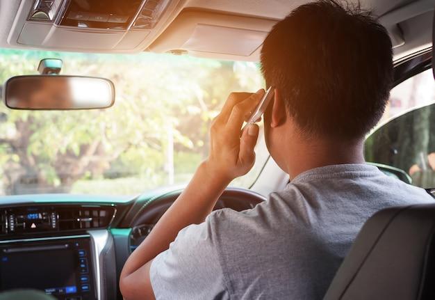 運転中の男性の携帯電話の使用