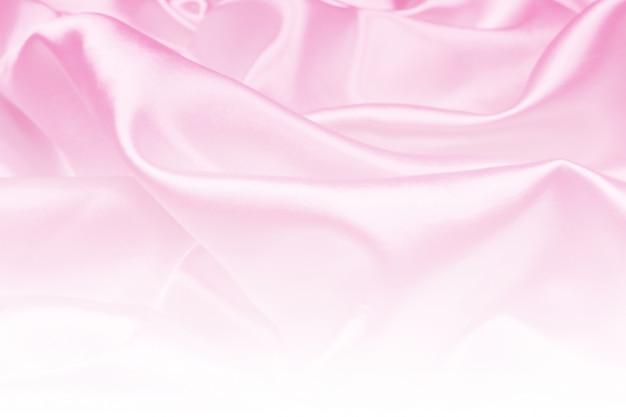 Красивая розовая атласная текстура ткани роскоши можно использовать как свадебный фон, ткань