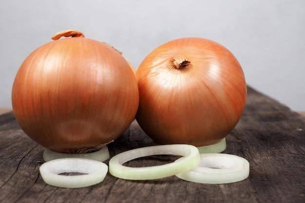 古い木製のテーブル背景に新鮮な玉ねぎと玉ねぎのスライス。自然食品