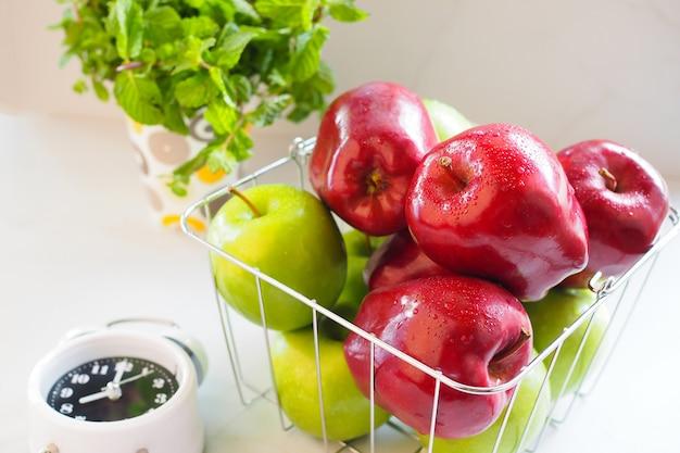 Красное яблоко и зеленое яблоко в корзине на белом столе