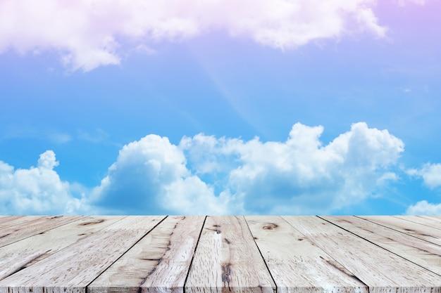 白い雲と青い空を背景に美しい空の木の板テーブルトップ。あなたの製品のモンタージュ