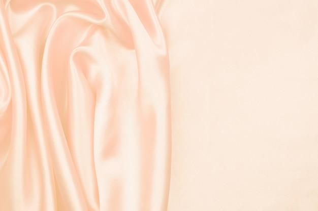 抽象的な背景のクリームシルクのテクスチャ豪華なサテン