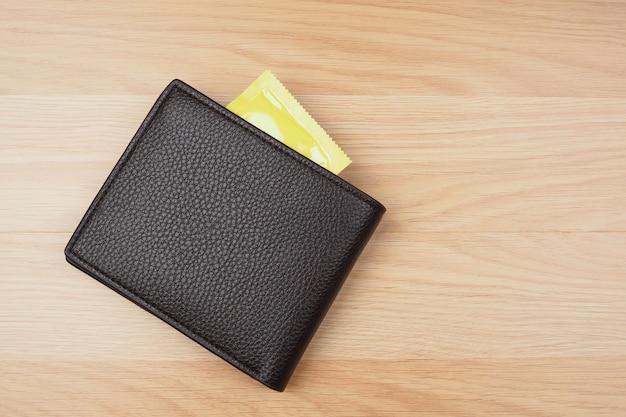 Желтые презервативы в черном кошельке на фоне деревянного стола