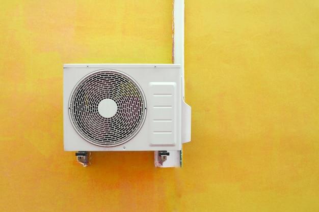 黄色の壁の背景の近くのエアコンコンプレッサー