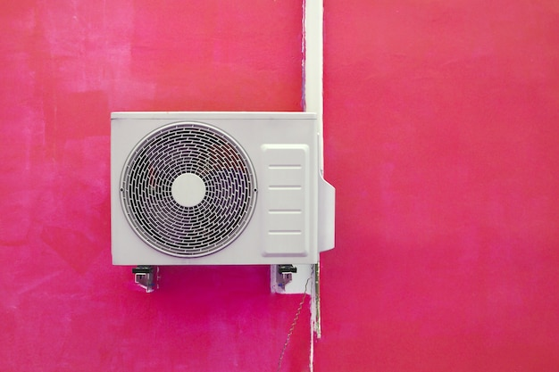 ピンクの壁の背景の近くのエアコンコンプレッサー