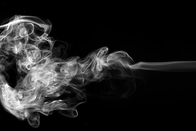 黒い背景に白い香を吹きましょう。火のデザインと暗闇のコンセプト