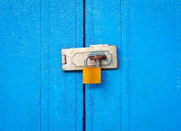 青い木製のドアのチェーンでロックされた南京錠背景